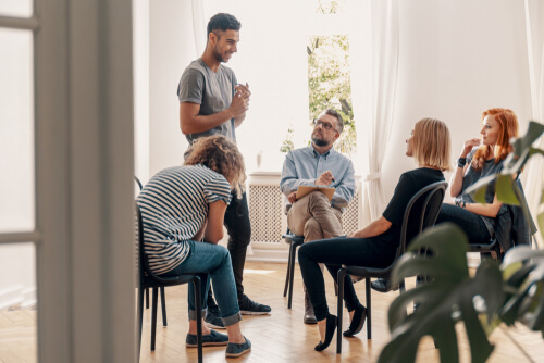 man standing surrounded by peers at group therapy