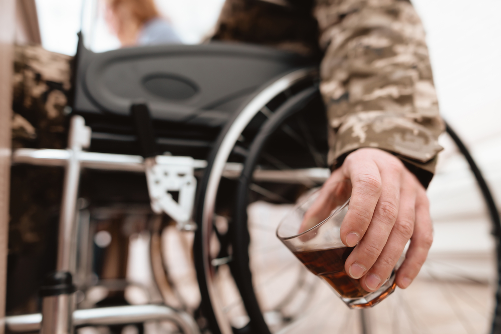 veteran in wheelchair holding glass of alcohol